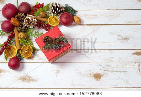Christmas Potpourri background with a boxed gift with room for Copy Space on wood plank board. Potpourri consists of pomegranates oranges nuts walnuts pine cones berries and cinnamon sticks