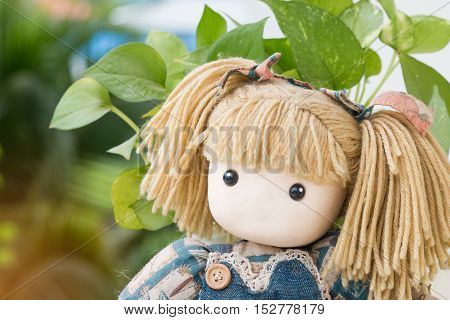 girl doll sitting funny pig-tailed headed doll in outdoor garden