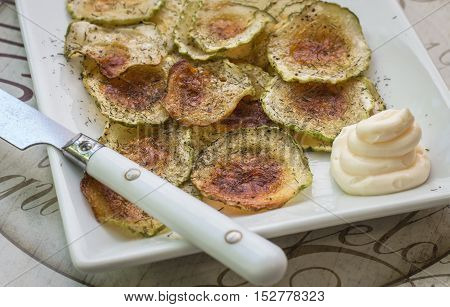 horizontal image of freshly baked warm plate of zucchini  chips in a white plate sprinkled with dill and parsley and a knife and a dip for the chips on the side.
