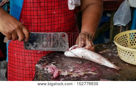 The woman Scale and clean fish for sell at market.