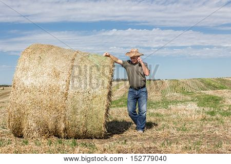 horizontal image of a farmer wearing a cowboy hat leaning against a big hay bale talking on his cell phone under a bright blue sky in the fall time