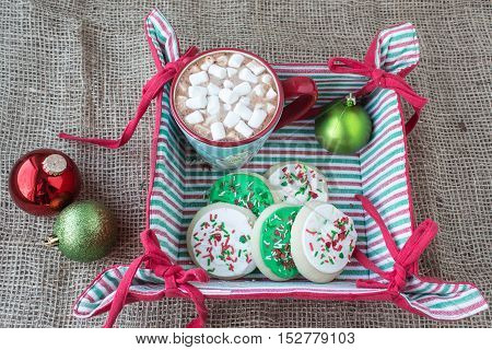 horizontal image of a cloth christmas basket  with a cup of hot chocolate and some short bread cookies covered in white and green icing with sprinkles on a burlap background with two christmas balls.