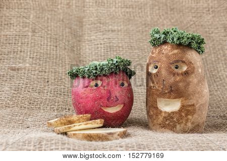 horizontal image of a red potato and a white potato with faces carved into them with kale pieces depicting the head of hair on burlap background with room for text.