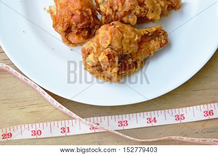 fried chicken leg and measuring tape for check waistline after eat