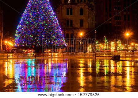 The big lighted Christmas tree in Syracuse NY reflected in the wet skating rink on Clinton Square