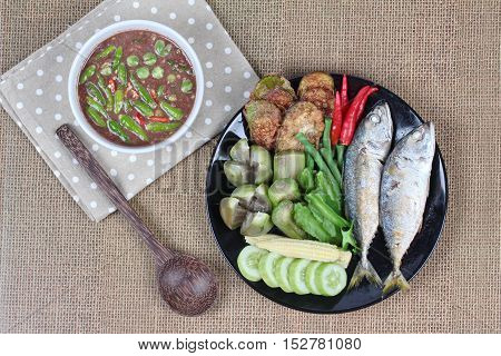 Thai local popular food as spicy shrimp paste dip (Nam Prik Kapi in Thai) served with side dish as deep fired mackarels,boiled long-eggplant,lentils,winged bean ,red hot chili pepper and cucumber.