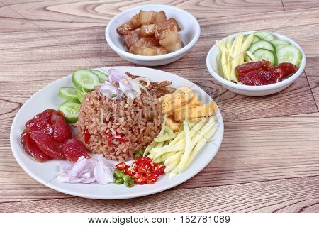 Thai food ,Fried jasmine rice with shrimp paste,(Kao Klok Kapi) with green mango roll,Chinese sausage,crispy dried fish,shrimp,chili,shallots,stir sweet pork,cucumber and scrambled egg .
