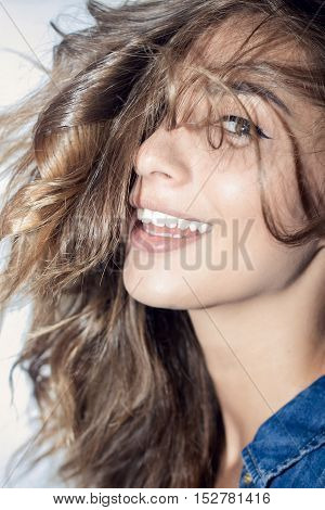 Fashion portrait of young pretty hipster woman with blonde hairs and big full bright lips wearing stylish black outfitdenim swag shorts white background. emotional portraits