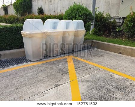 Clear garbage bin on concrete floor in car parking.
