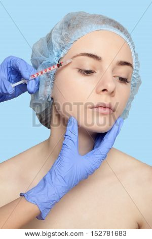 Attractive young woman gets cosmetic injection an injection in the upper lip over blue background. Doctors hands making an injection in face close-up. Beauty Treatment. injection in the eyelid