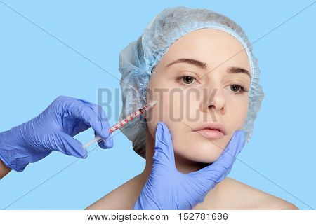 Attractive young woman gets cosmetic injection an injection in the upper lip over blue background. Doctors hands making an injection in face close-up. Beauty Treatment. shot in the cheek