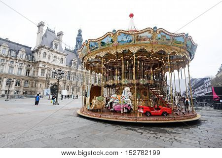 PARIS - MARCH 17, 2015: People and vintage carousel at Hotel de Ville in Paris, France on gloomy day MARCH 17, 2015