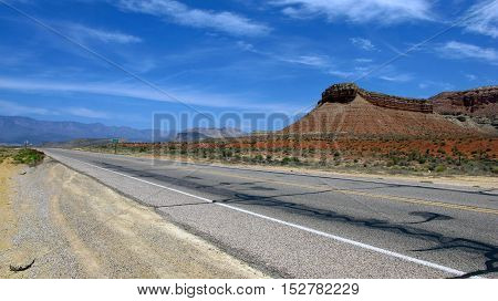 A deserted road through the vast plains and wild lined with mountains of Utah, USA. Light, natural colors.