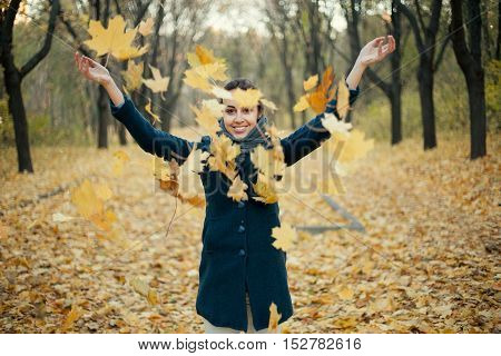 Woman throwing yellow leaves in the air