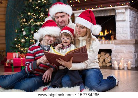 Family read stories sitting on sofa in front of fireplace in Christmas decorated house interior
