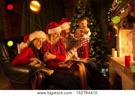 Happy family sitting on sofa while reading a story book in Christmas decorated room at home