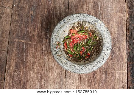 chilli pepper in stone mortar on the wooden table paste spicy herb ingredient food Thailand ancient style. Image Top view