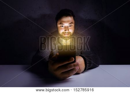 Mad man with mobile phone in dark room