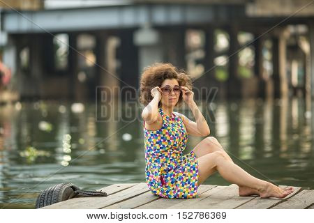 Young Asian woman in sunglasses sitting on a wooden river pier.
