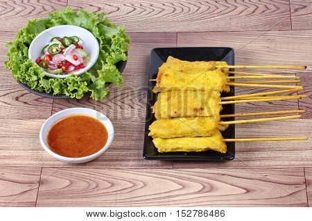 Charcoal boiled pork satay on butcher served , home made in big size, served with Thai cucumber chili sauce  ( Ar Jad in Thai) and nut sauce are popular Asia cuisine.