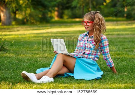 Lovely attractive girl with a laptop. She sits on a green lawn in the park. A student takes a break from lessons.