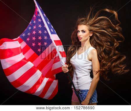 Young attractive girl holding a US flag on the flagpole. She a T-shirt and shorts with a print of the flag. Long curly hair. Portrait of a real patriot. The Star Stripes.