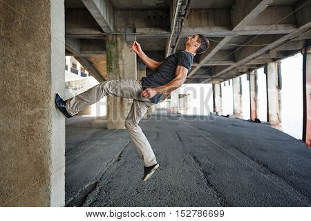 Men T-shirt of parkour in urban space. He runs up the wall. Sport in the city. Movement is life.