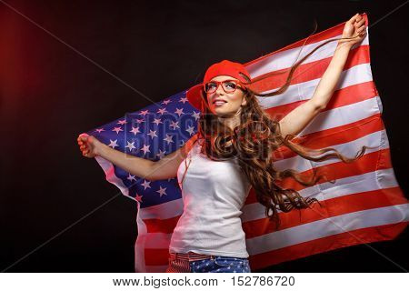 Young attractive girl in a baseball cap and sunglasses holding a US flag. She a T-shirt and shorts with a print of the flag. Long curly hair. Patriot country.