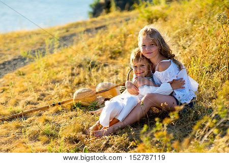brother and sister on picnic sitting on green grass warm summer vacations close up