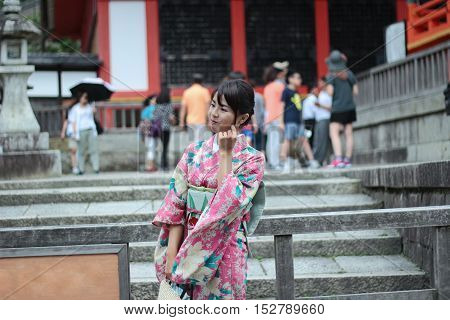 Kyoto,Japan-June 26,Women's kimonos post and smile for photo within Fushimi Inari shrine on June 26,2016 in Kyoto,Japan. Selective focus at wowan.
