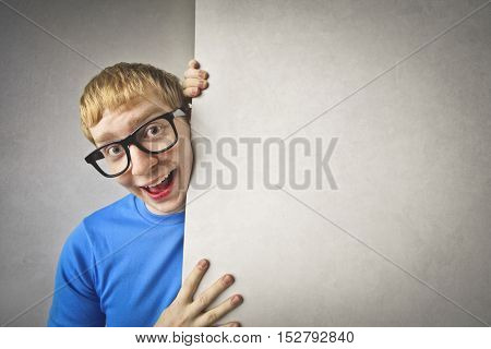 Cheerful guy holding a blank board