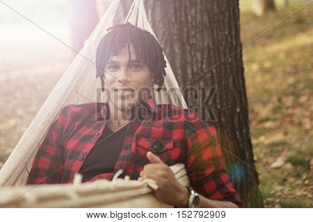 Smiling young man on a hammock