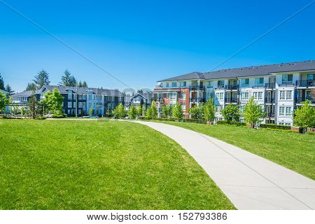 Concrete pathway across huge green lawn in front of residential condo building. Apartment building on sunny day with blue sky.