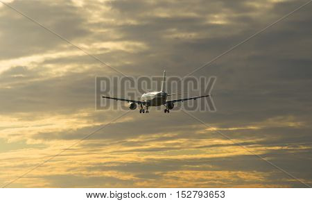 The plane flies at sunset in a cloudy sky