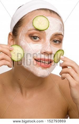 Beautiful woman is applying cucumberon her face with cosmetic mask