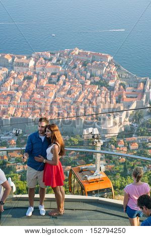Dubrovnik, Croatia - July 21, 2016: beautiful couple making selfie on the observation deck of cableway on the background of the old town of Dubrovnik