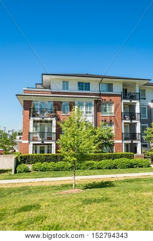 Brand new low rise apartment building with concrete pathway and small tree in front on sunny day in British Columbia Canada