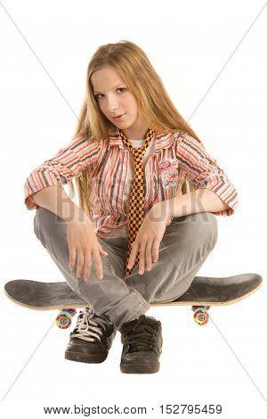 Teenage girl is sitting on skateboard isolated on white background