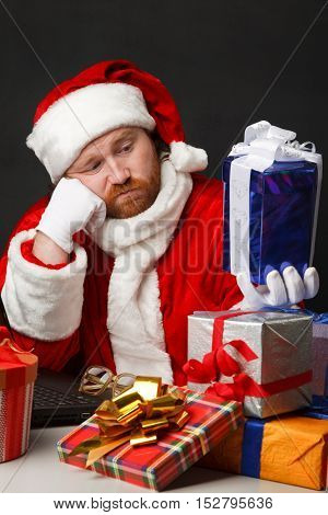 Thoughtful man in santa costume is looking at present