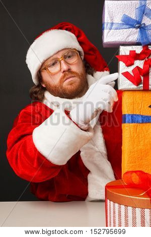 Thoughtful man in santa costume is counting presents