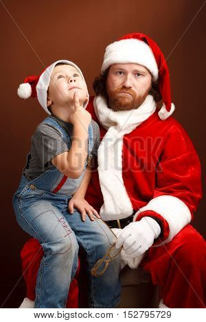Boy is sitting on Santas knee and thinking about his future present. Mandressed in Santa costume looks tired and unhappy
