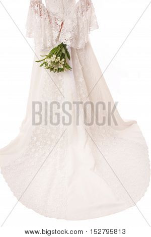Back view of brides lace wedding dresswith bunch of flowers in her hand