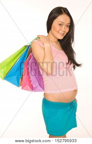 Young pregnant asian girl with the shopping bags on the white background