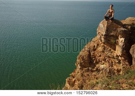 Real yoga instructor practicing on the rock near water line.Copyspace