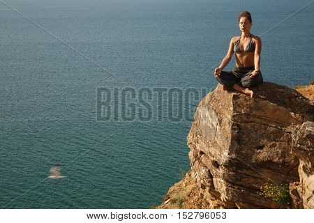 Woman meditating on the rock near water line.With flying seagull