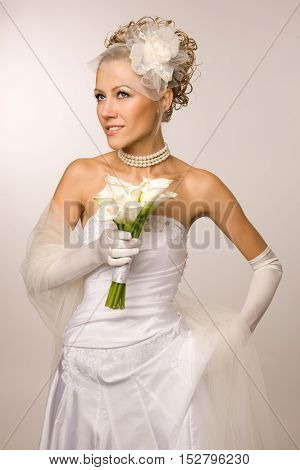 Young beautiful smiling bride looking up with Calla lily bouquet