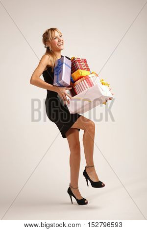 Cheerful young woman is balancing on one leg with heap of gifts