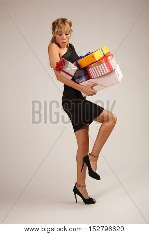 Cheerful young woman is balancing on one leg with heap of gifts and loosing one