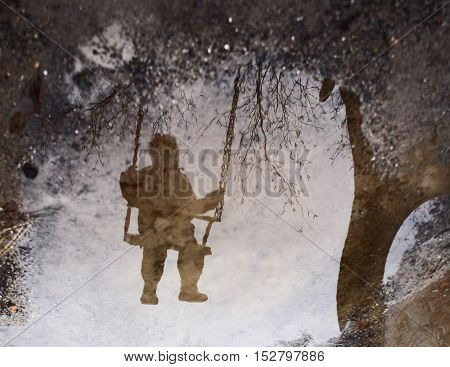 Inverted reflection of a child on a swing