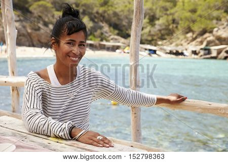 Middle aged couple smiling across a table by the sea, Ibiza